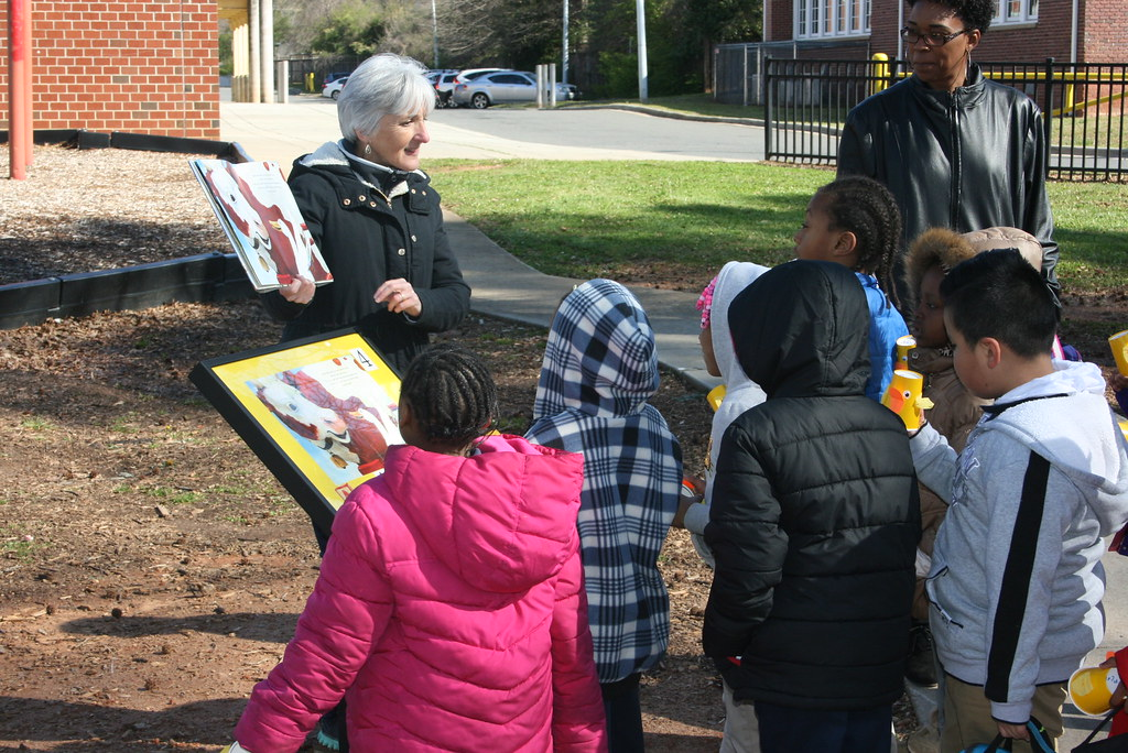 Photograph of librarian reading a story during a StoryWalk to a group of children.