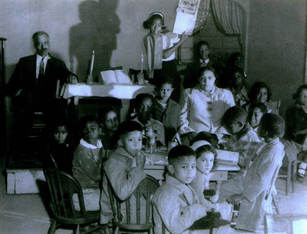 Black and white photo of children around a table at Sunday School.