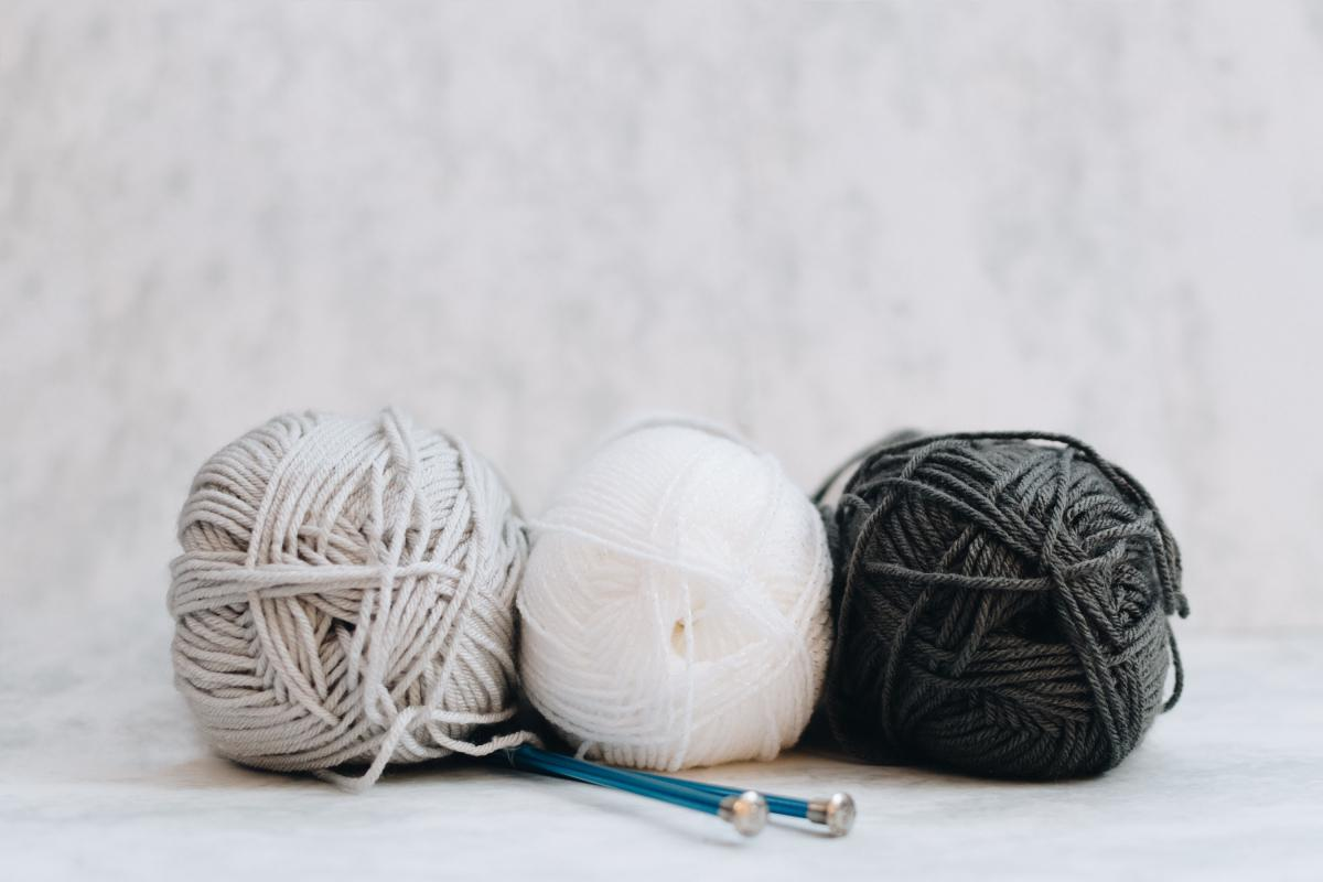 three spools of yarn, black, white and gray, sit with a pair of blue knitting needles.