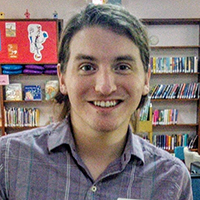 Austin Jenkins smiling toward camera in library