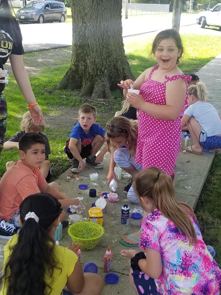 A girl in a pink dress standing among a group of kids sitting on the sidewalk making slime
