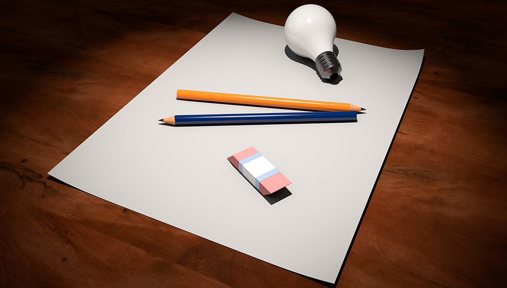 Piece of paper, light bulb, pencil and eraser