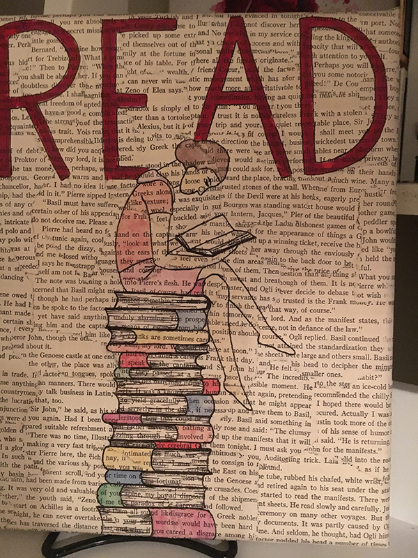 "A page from a book with the word ""read"" drawn on it in red marker with a drawing of a girl sitting on a stack of books."