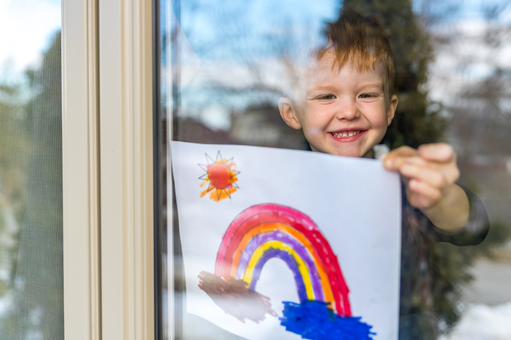 A child hanging a painting of a rainbow inside a window
