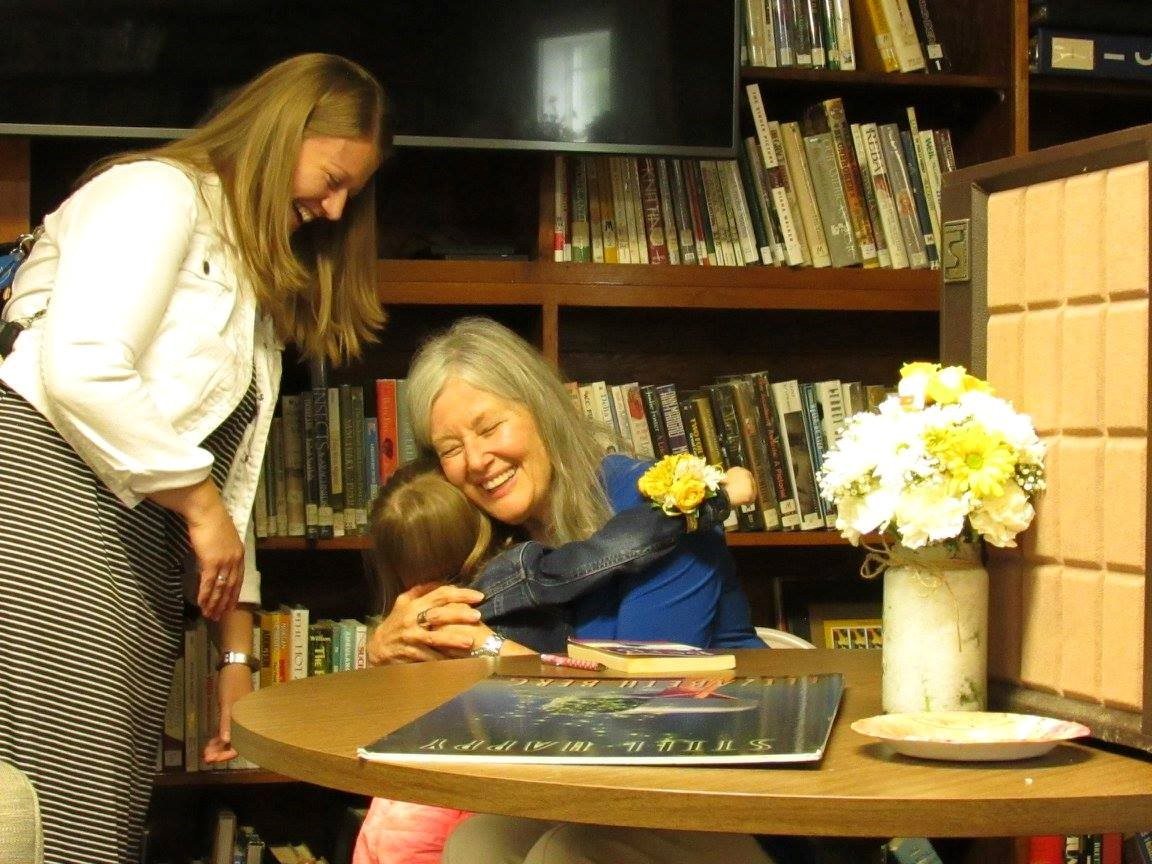 Author Elizabeth Berg hugs a girl at the library