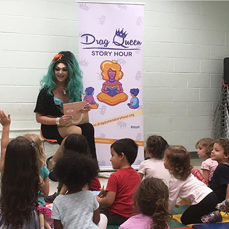 "Drag Queen sits in front of audience of children holding a book smiling. A child raises their hand to ask a question. A poster reads ""Drag Queen Story Hour"" in the background."