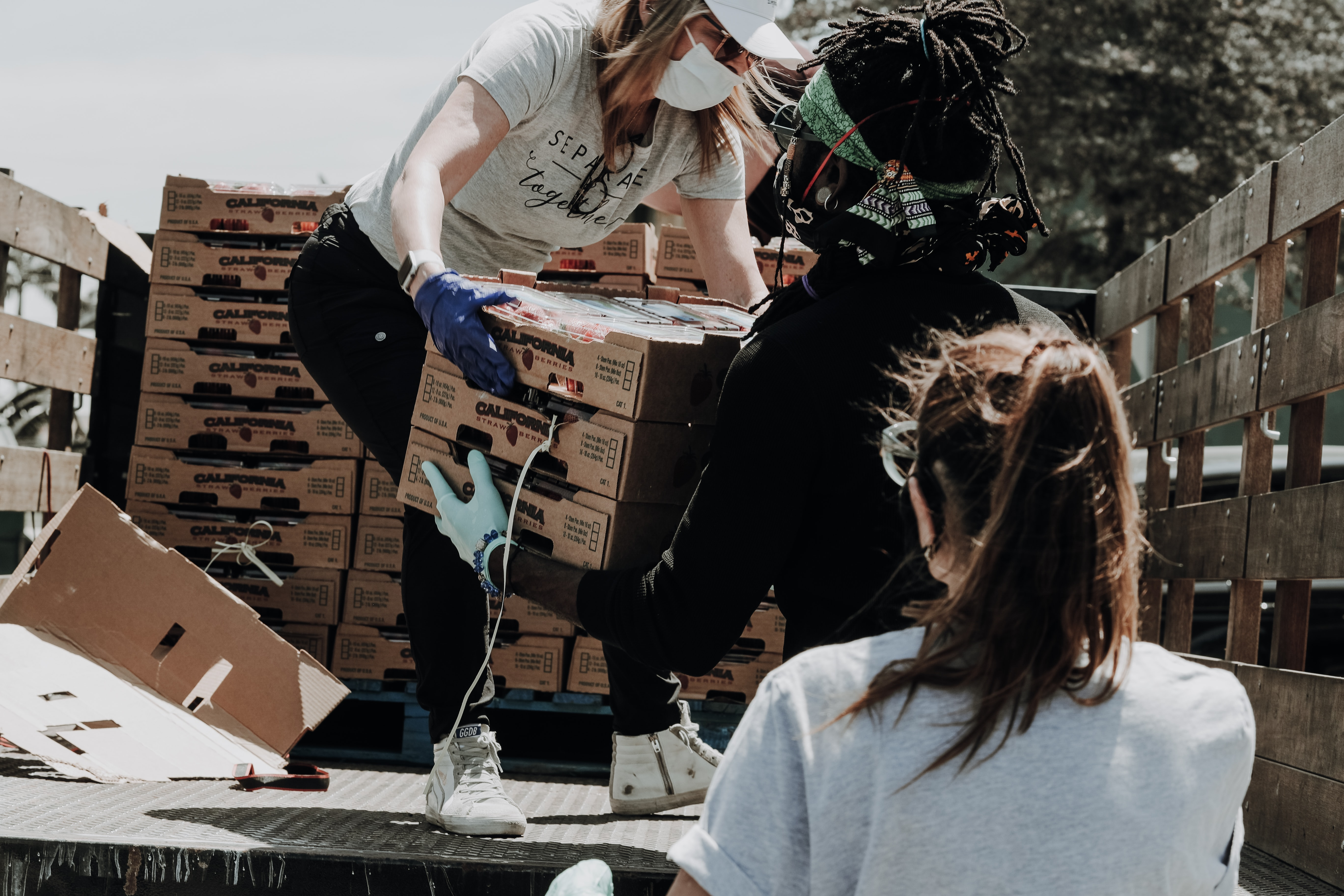 Person passing boxes of food off a truck