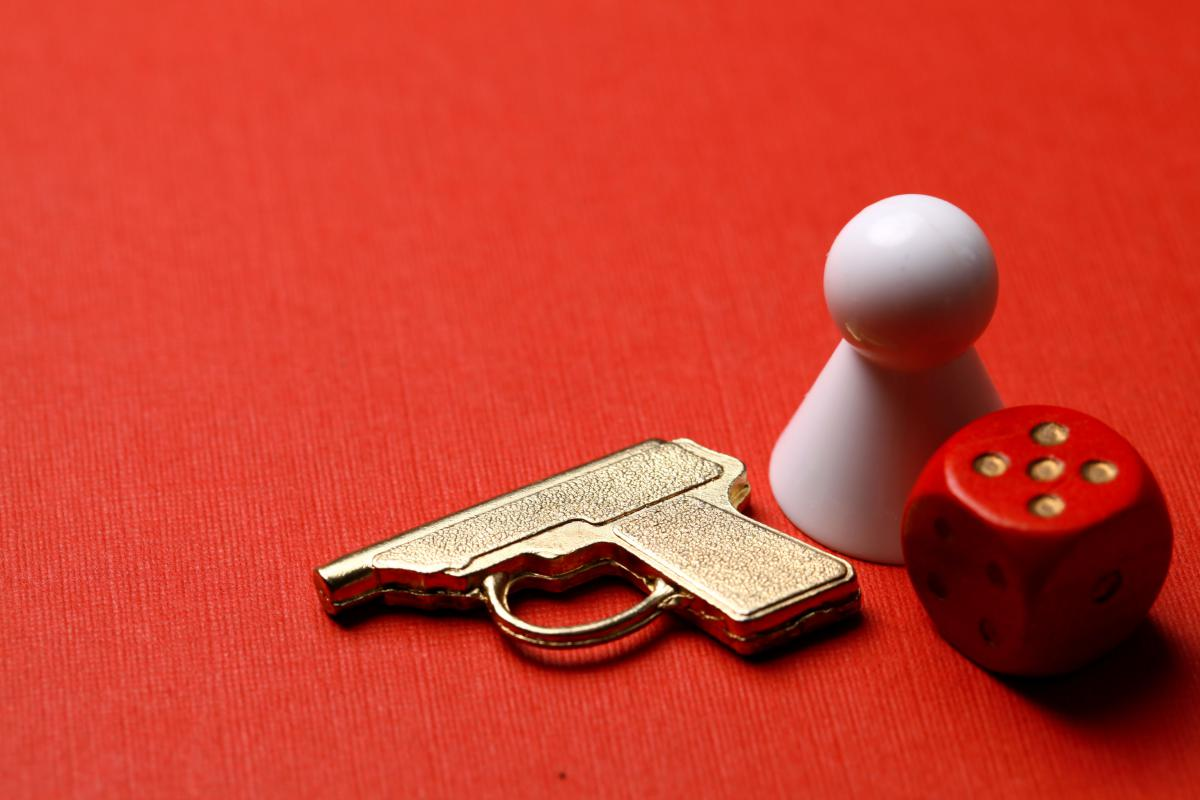 Red background with a white board game piece, a piece shaped like a gun and a red and white dice.