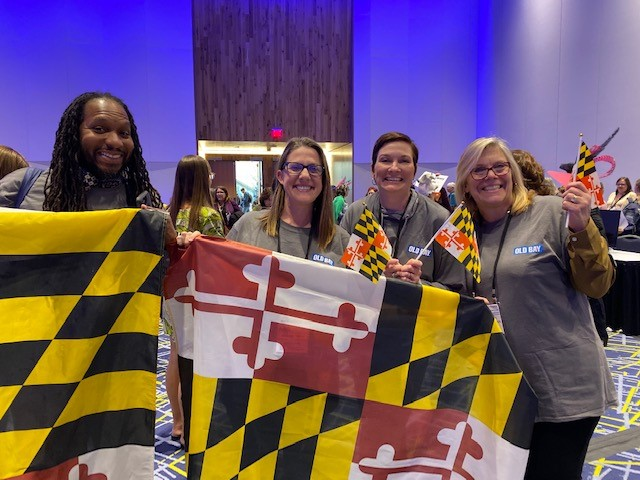 Four conference attendees holding the Maryland state flag