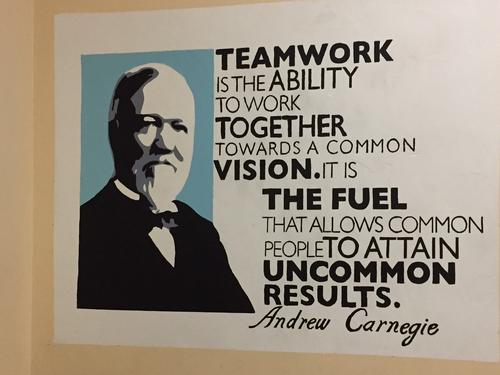 "Sign that reads ""teamwork is the ability to work together towards a common vision. It is the fuel that allows common people to attain uncommon results."""
