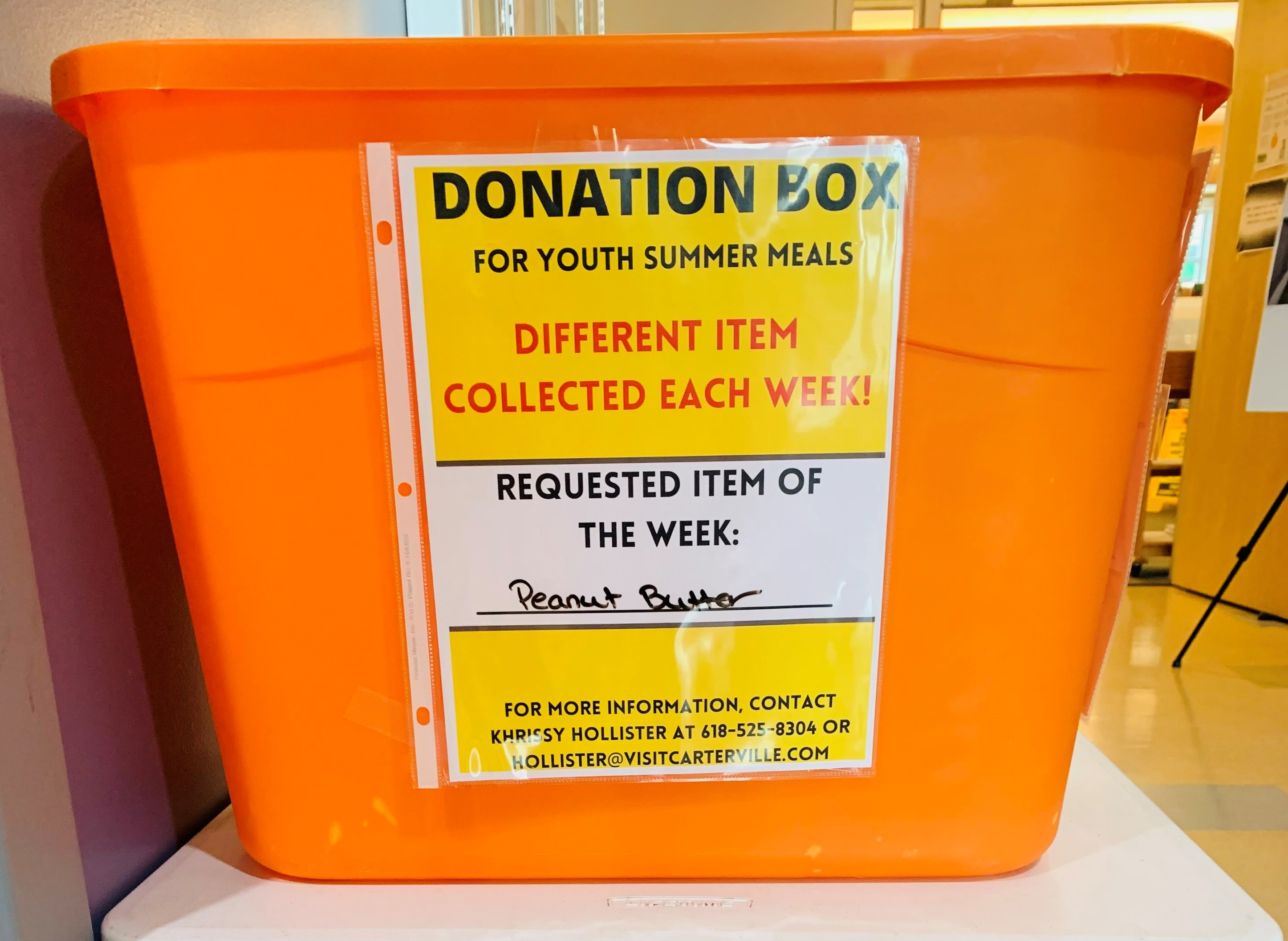 Photograph of bright orange donation box. Text on box reads: Donation Box for Youth Summer Meals