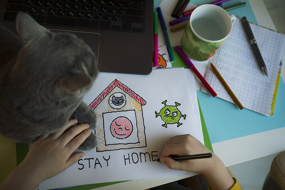 "Photo of a child drawing a picture titled ""Stay home"""