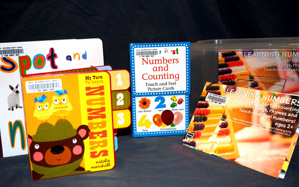 A plastic tub sits with with four book in front of it about learning numbers.