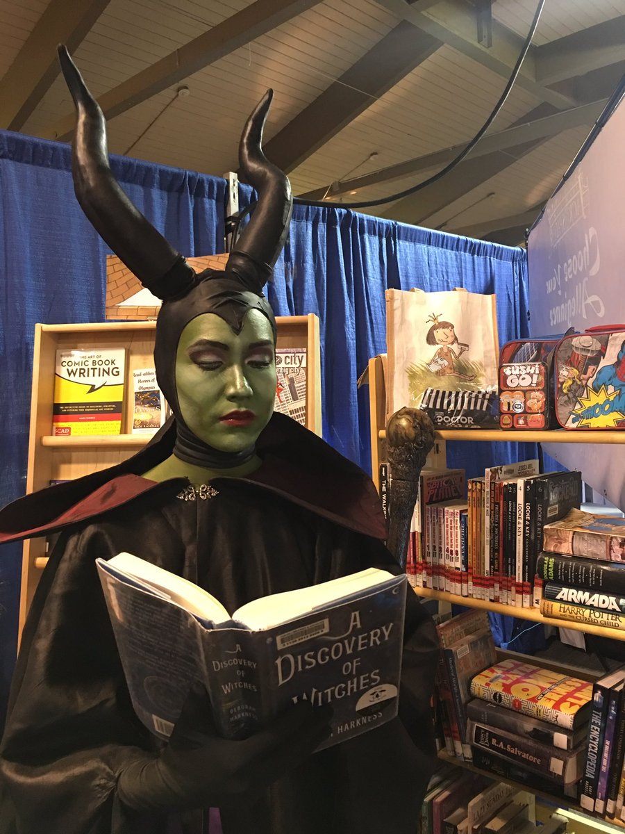 Maleficent reading a book at the booth