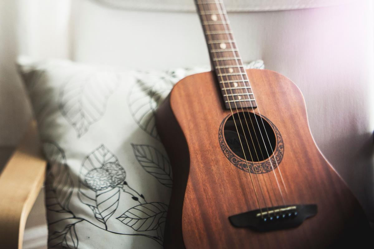 A wooden guitar sitting on a chair with a green pillow behind it.