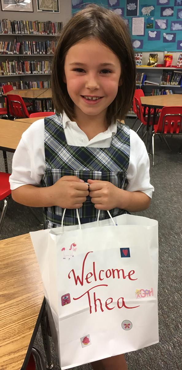 "Young girl stands in a library smiling, holding a paper bag that reads ""Welcome Thea"""