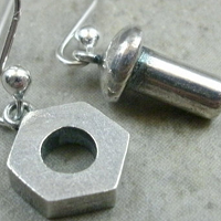 close-up of earrings made with nuts and bolts