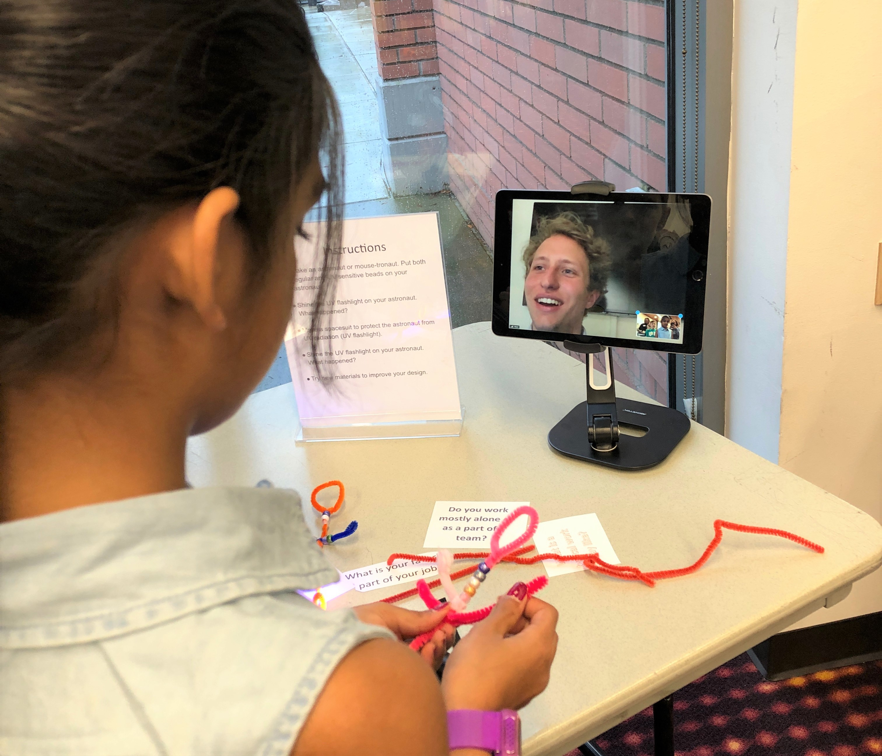 Photo of a child speaking with a scientist on a tablet.