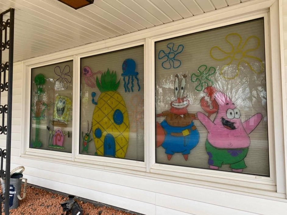 A photo of windows with Spongebob Squarepants characters painted on.