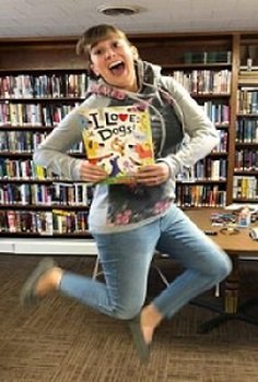 "Chelsea Price jumps while holding a book called ""I Love Dogs"""