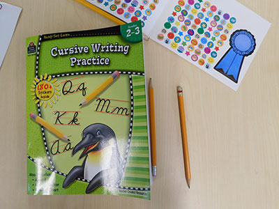 A cursive writing practice workbook and some stickers