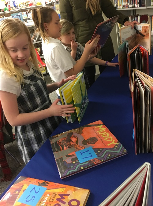 Students peruse books on a table