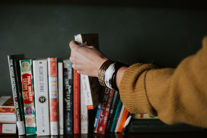 Hand reaching out and selecting a book from several on a shelf
