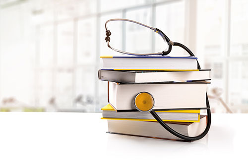 Stethoscope wrapped around a stack of books