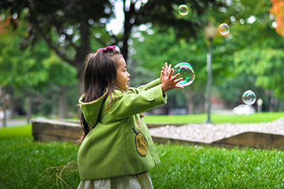 A young girl plays with bubbles in a park