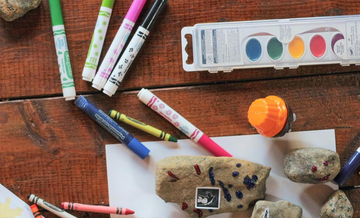 Photo of markers, crayons, paint on a table.
