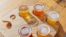 a flight of beers on a wooden tray