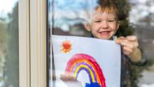 A child hanging a painting of a rainbow on the inside of a window