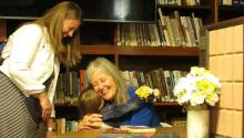 Author Elizabeth Berg hugs a girl at her Meservey Public Library visit