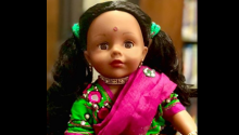 18 inch doll stands in a green a pink dress with pig tails in her hair and a bindi on her forehead.