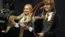 Two teens hold snakes at a Harry Potter Yule Ball