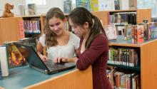 Two girls looking at a laptop in a school library