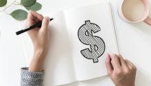 hand drawing dollar sign on white paper