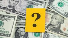 Photo of cash with a yellow question mark on top.