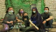 Photo of masked group in the escape room.