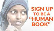 "A woman looks to her right at the words, ""Sign up to be a 'human book.'"""