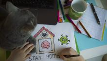 "A photo of a child drawing a picture titled ""Stay home"""