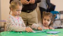 Girls making a craft at a Light Up the Holidays program