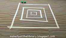 """A Skeeball game board taped to the floor, and two balls (from the activity """"Tape Games"""")"""