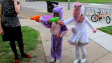 Children dressed as superheroes shoot squirt guns at a target.