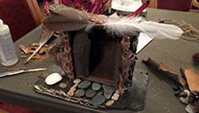 Fairy house created from slate, feathers and pinecones