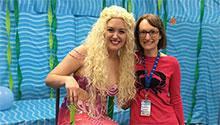 Children's librarian posed with the professional mermaid, smiling toward camera