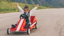 Young boy in Go Kart with upstreched arms