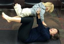 Woman holding toddler in airplane pose