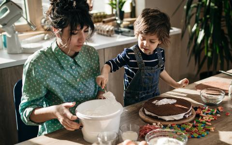 Photo of mother and child decorating a cake.