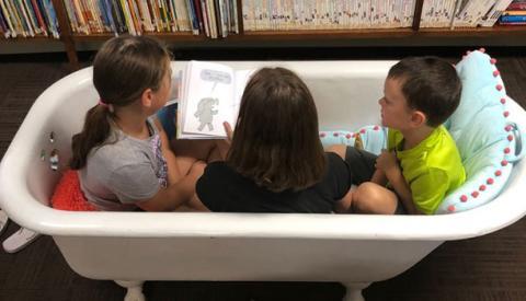 Three children reading in a bathtub